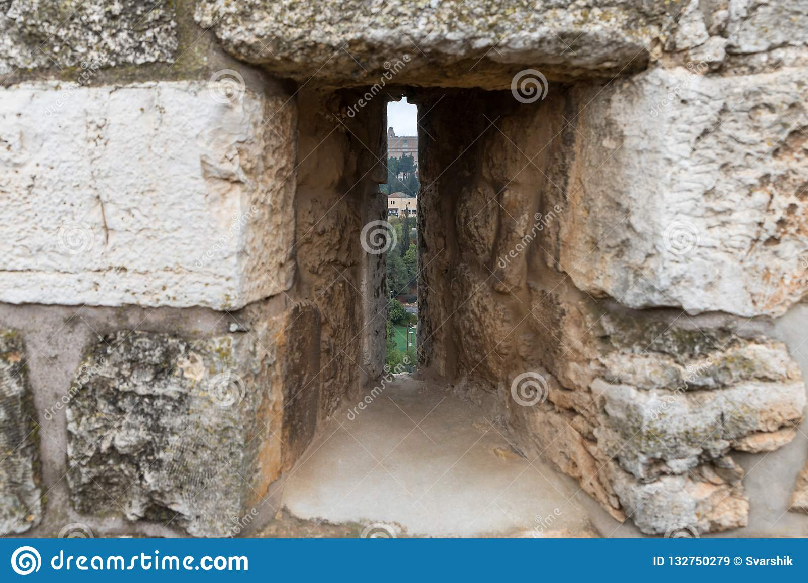 View through the closed loophole in the city`s fortress wall at the city near the Jaffa Gate in old city of Jerusalem, Israel