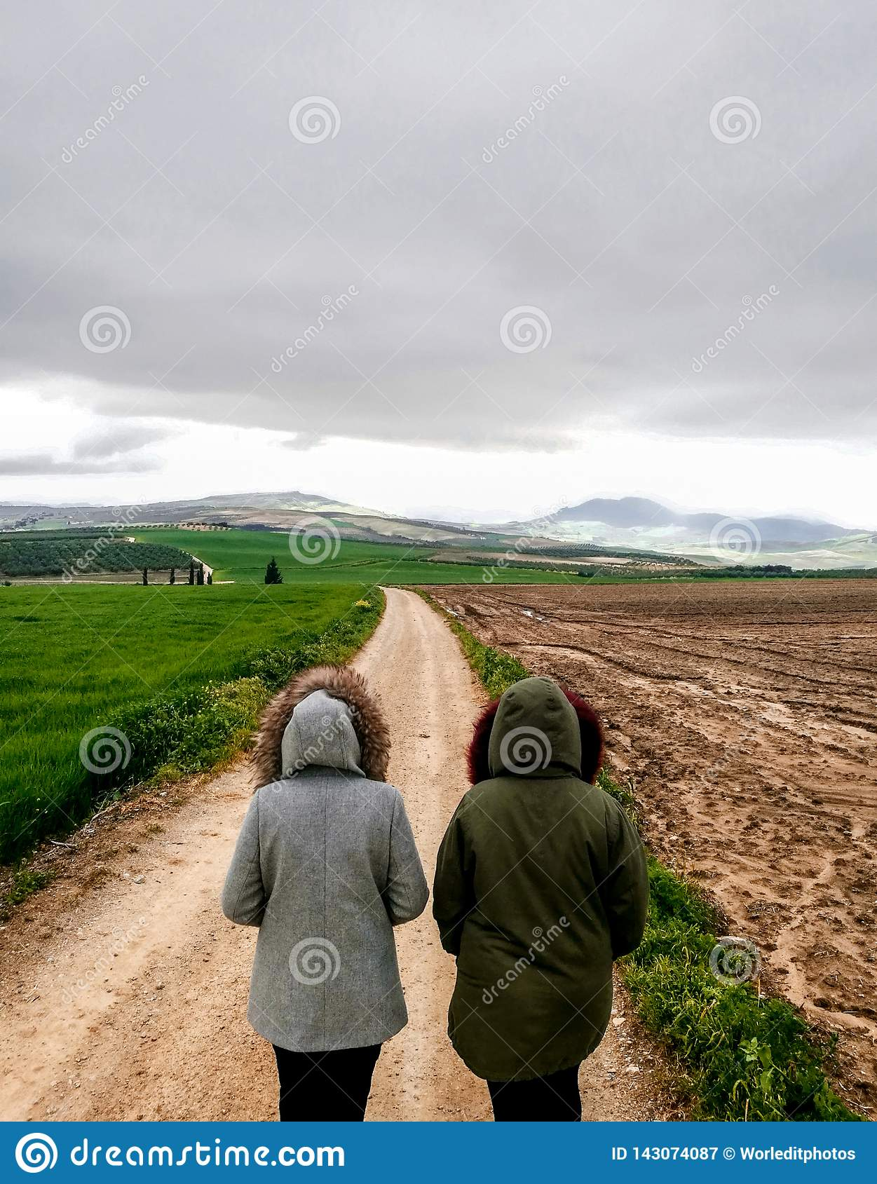 View of couple walking on a dirt road in beautiful parkland