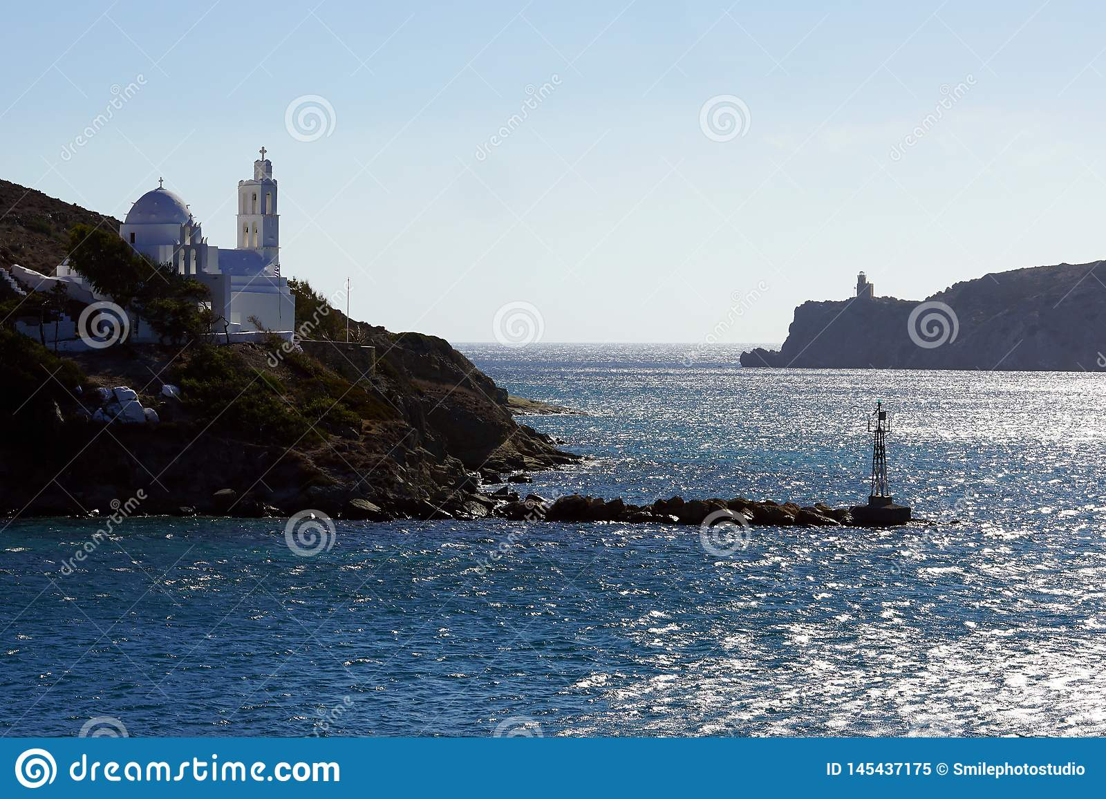 View of the entrance to the port of Ios with its lighthouse and the church of Saint Irene