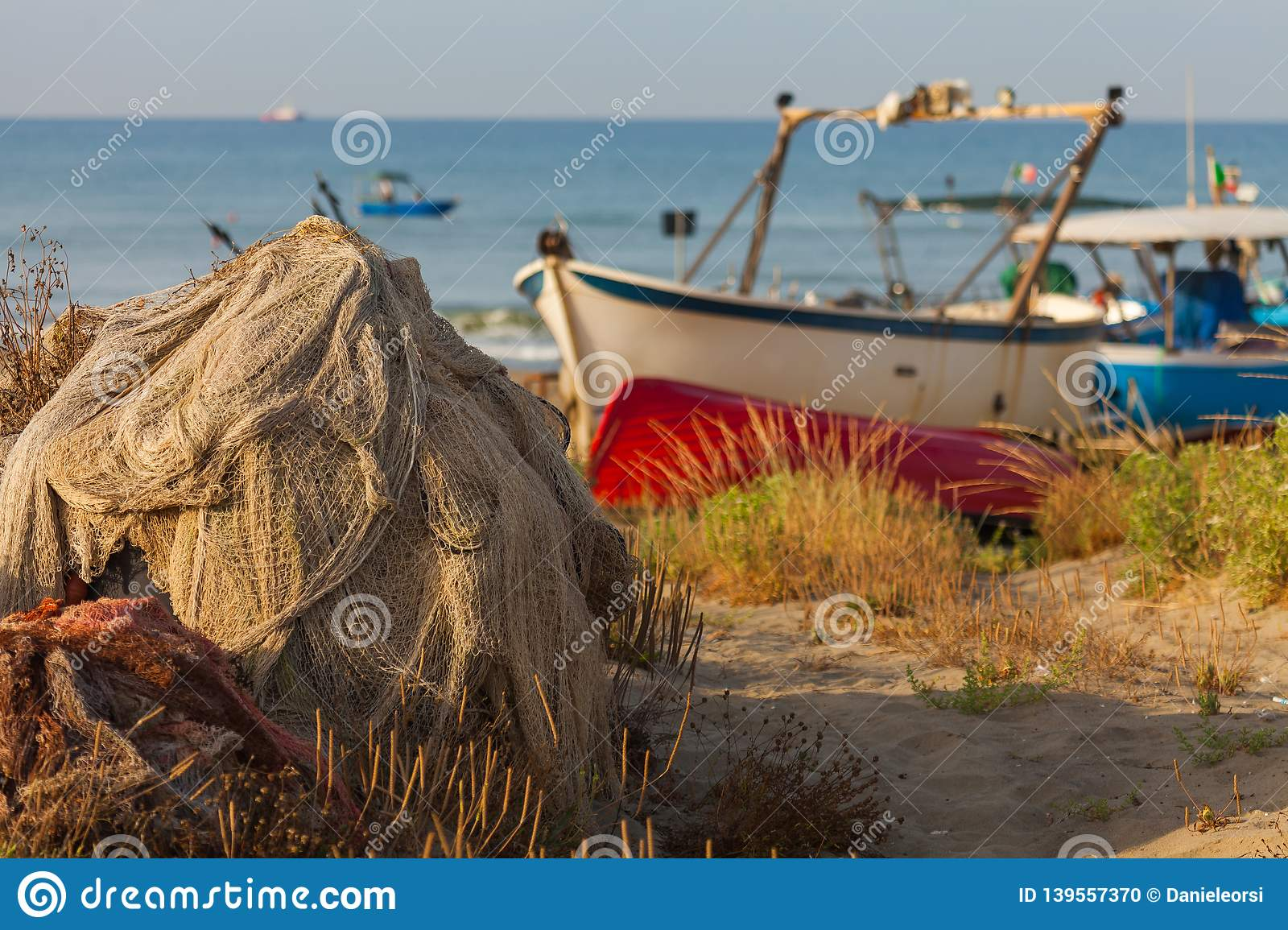 A view of a fishing net in front of the boat on the beach. Beautiful calm sea and water during an hot summer day