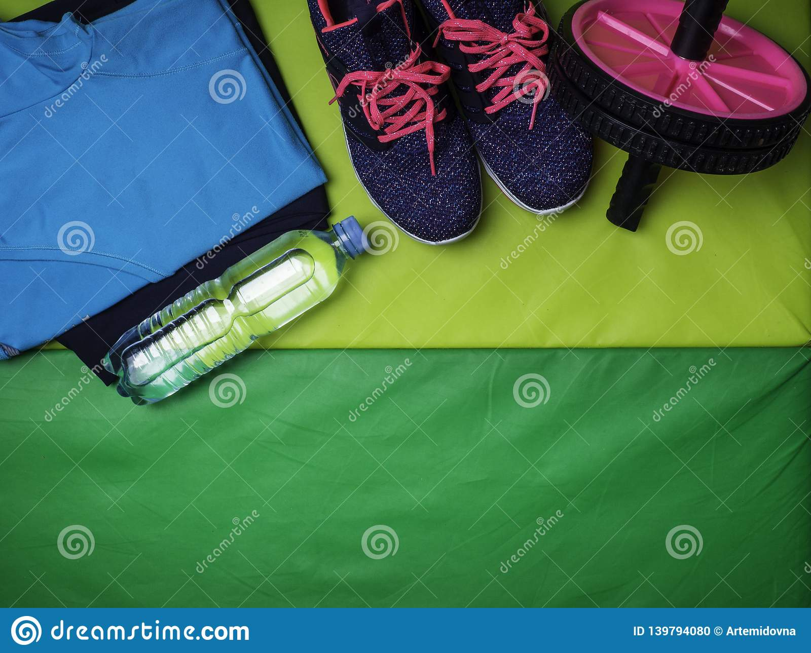 9d1dafc52df55 View of Fitness and sport equipment. Healthy lifestyle concept. Sneakers,  sportswear, roll, water on green mat background, top view
