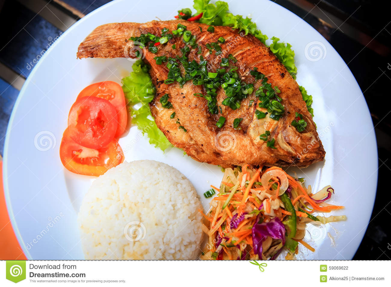 View of fried fish with rice vegetables on white plate for Baked fish and rice