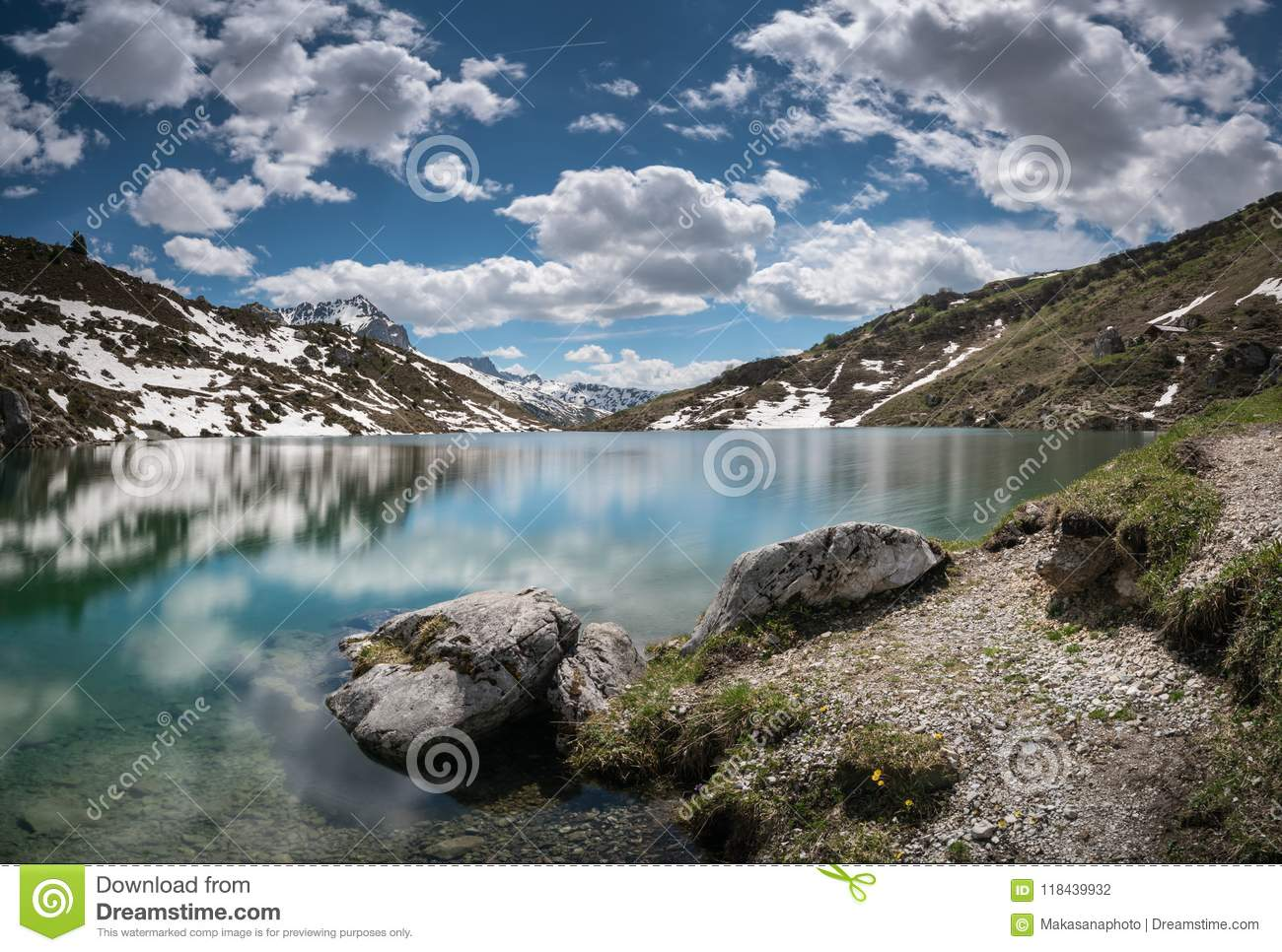 Gorgeous mountain lake in the Alps with reflections and snow remnants