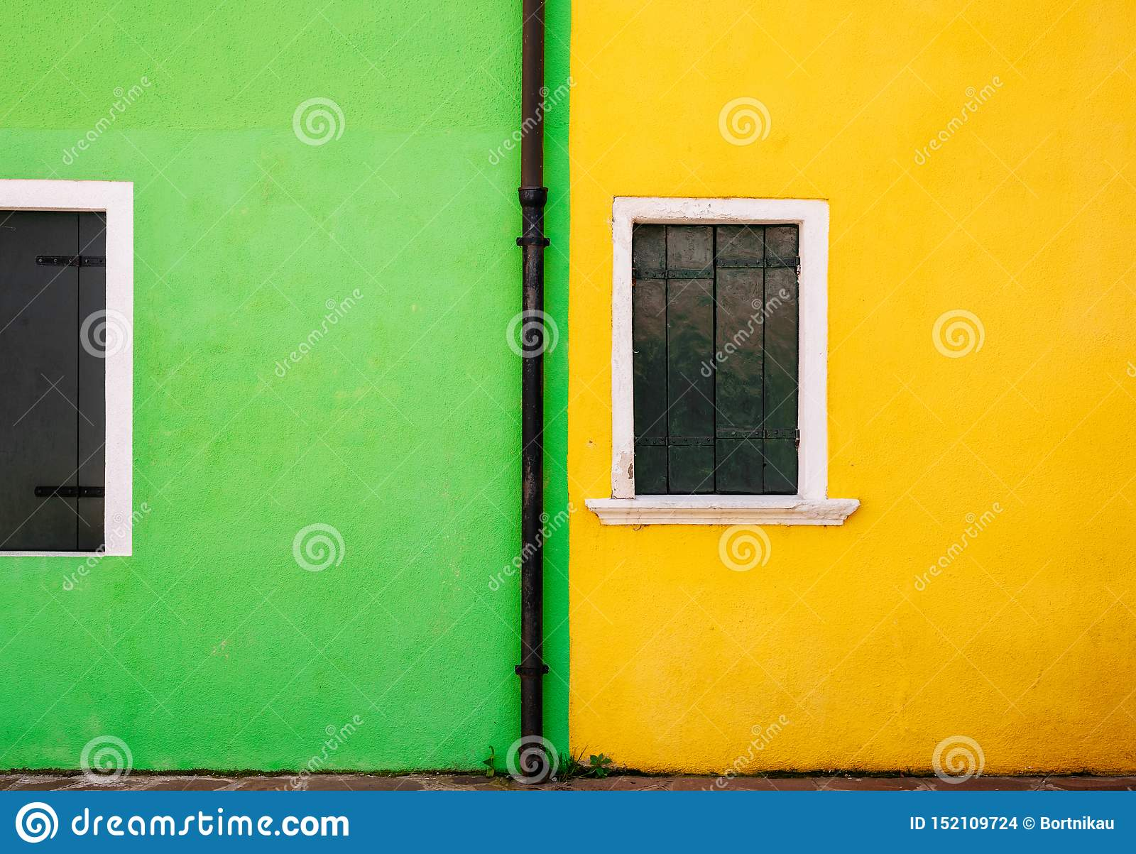 View Of Green And Yellow Stone House And Small White Windows