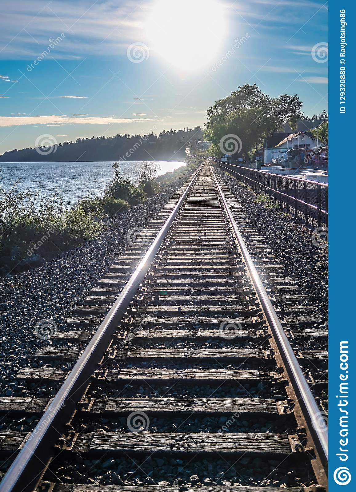 View of the length of railway track with glorious sunlight rays, river, distant mountains and greenery creating scenic landscape,