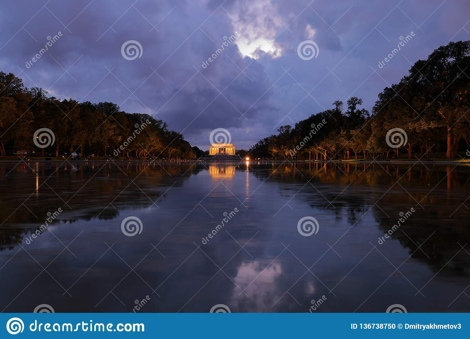 View of Lincoln Memorial and its reflection in Reflection pool at night with dramatic sky.