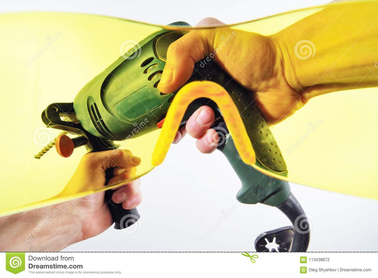 View Of Men`s Hands With An Electric Drill Through Yellow