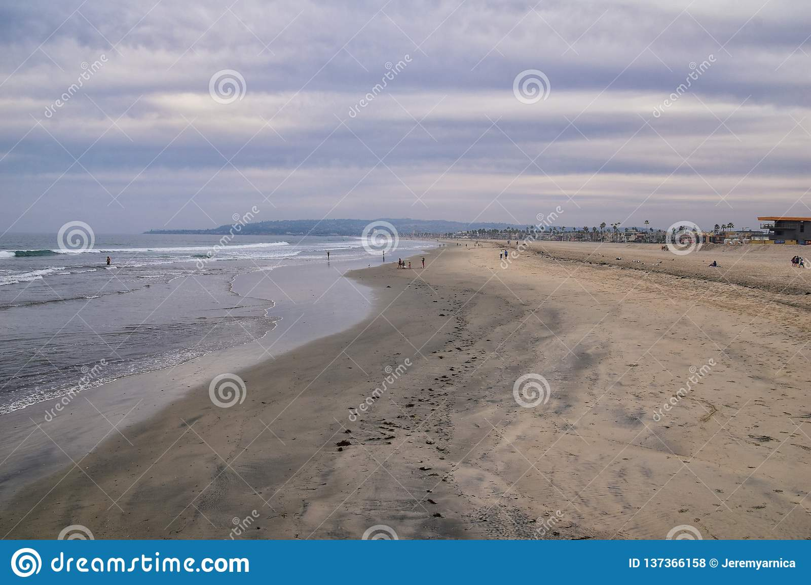 View from Mission Beach in San Diego, of Piers, Jetty and sand, around surfers, including warning signs, palm trees, waves, rocks,