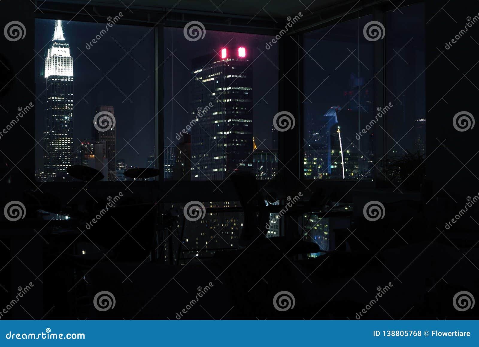View of night skyscrapers of New York City Manhattan through windows of apartment. Top view of night midtown of Manhattan.