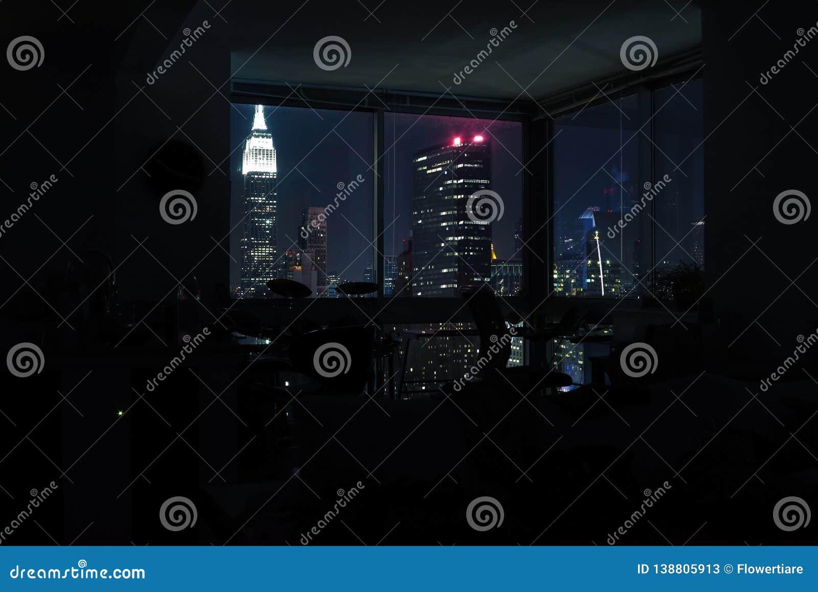 View of night skyscrapers of New York City Manhattan through windows of apartment. Top view of night midtown of Manhattan. USA