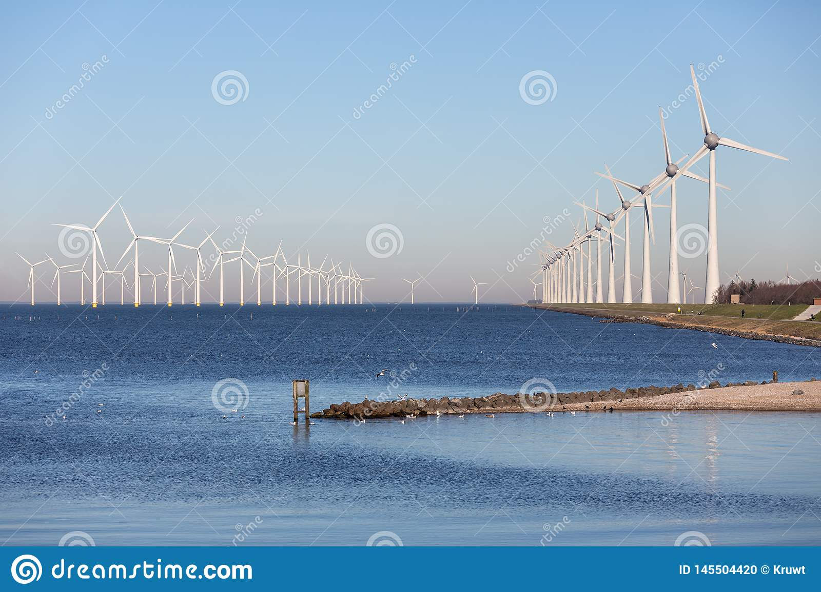 View at off shore wind turbine farm from beach Urk
