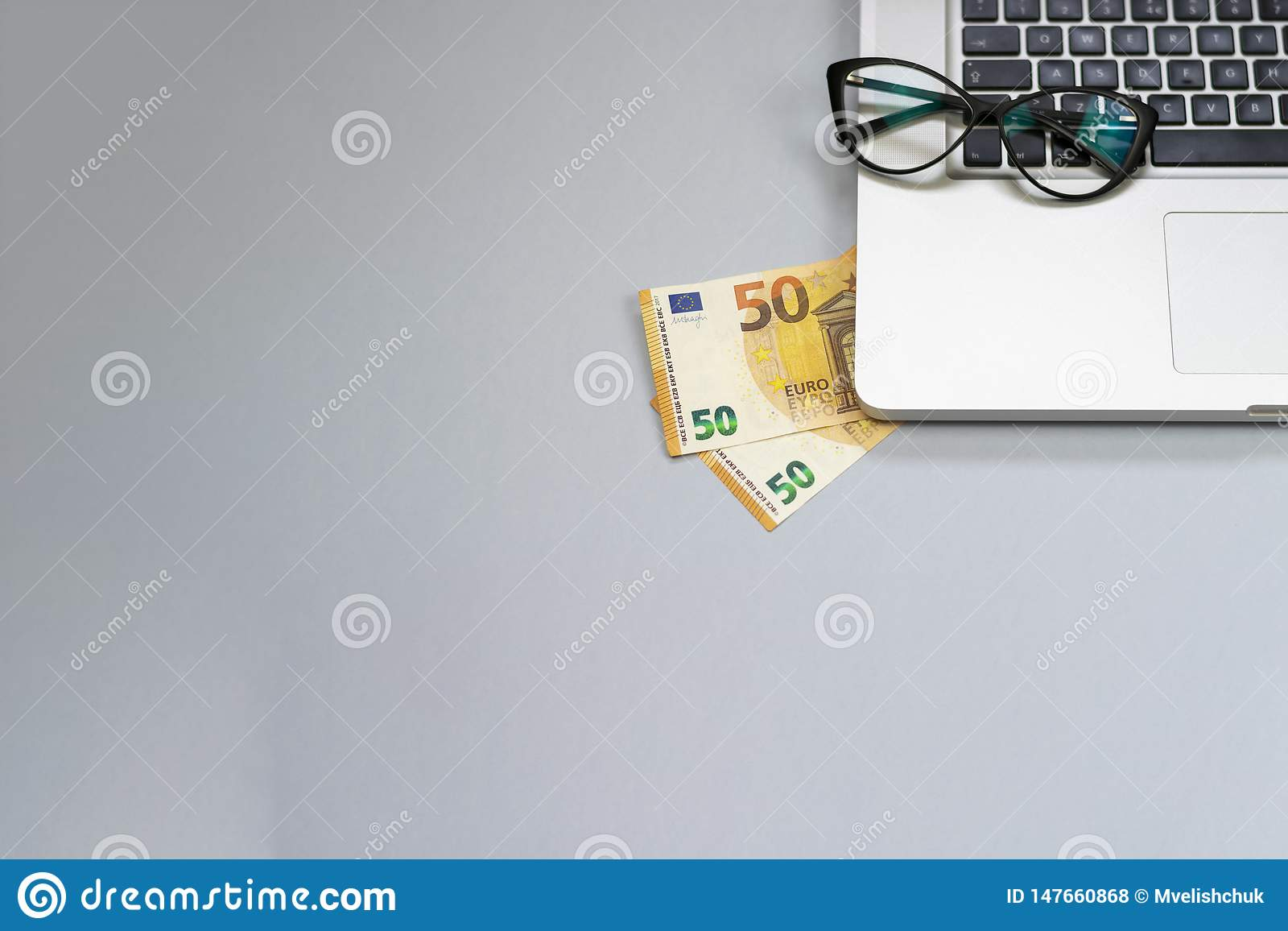 desk with money, laptop, glasses