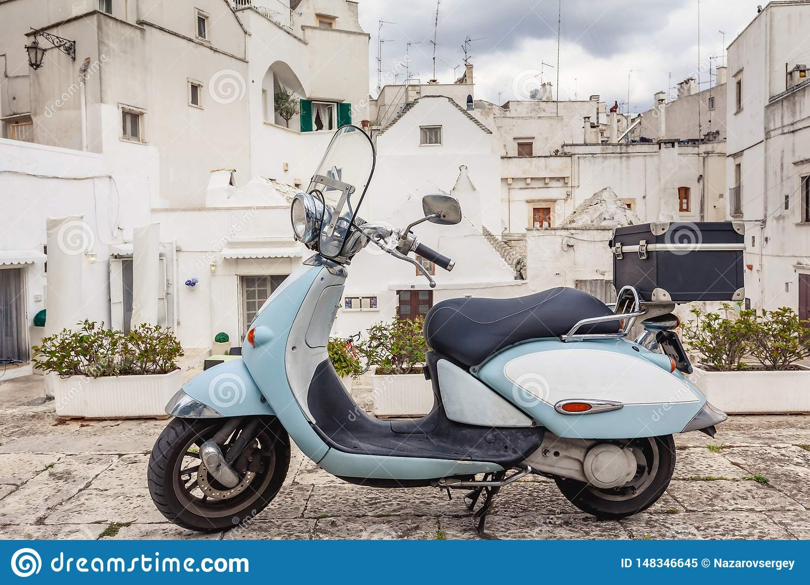 View of the old town of Martina Franca. Classic blue moped on the background of an anient buildings.