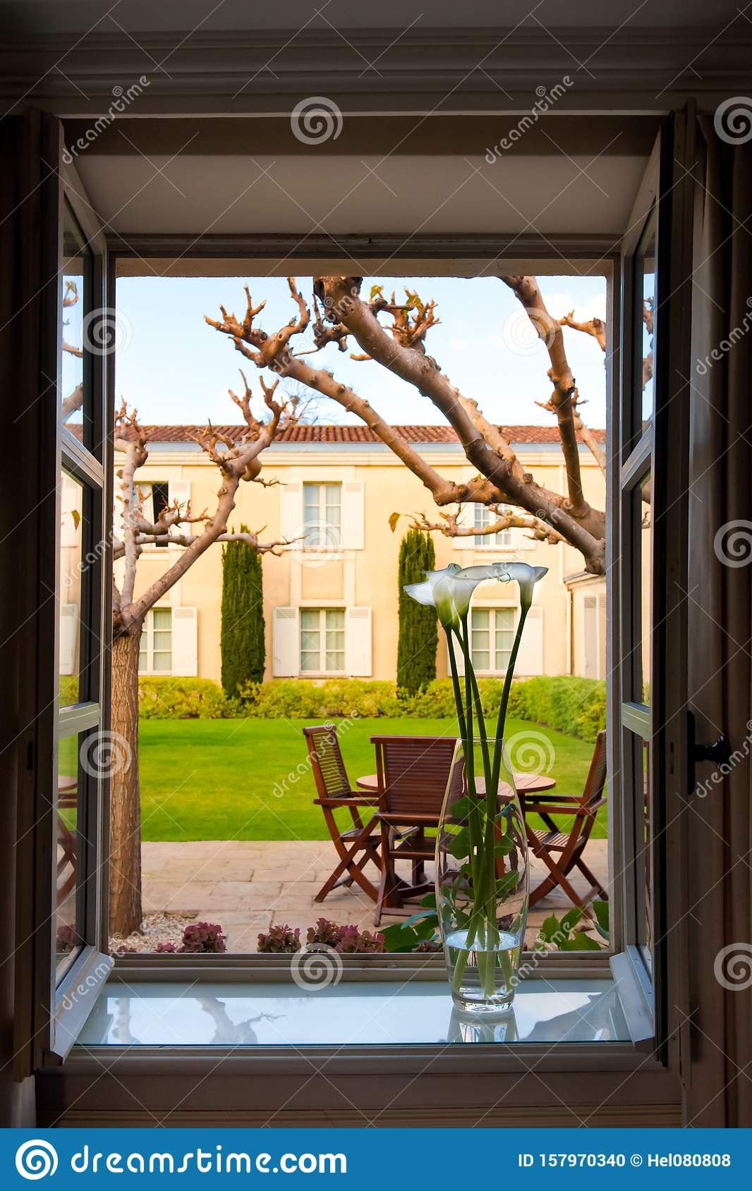 View out of opened window with vase on sill to backyard with patio, formal garden of Chateau Cordeillan-Bages, Bordeaux, France.