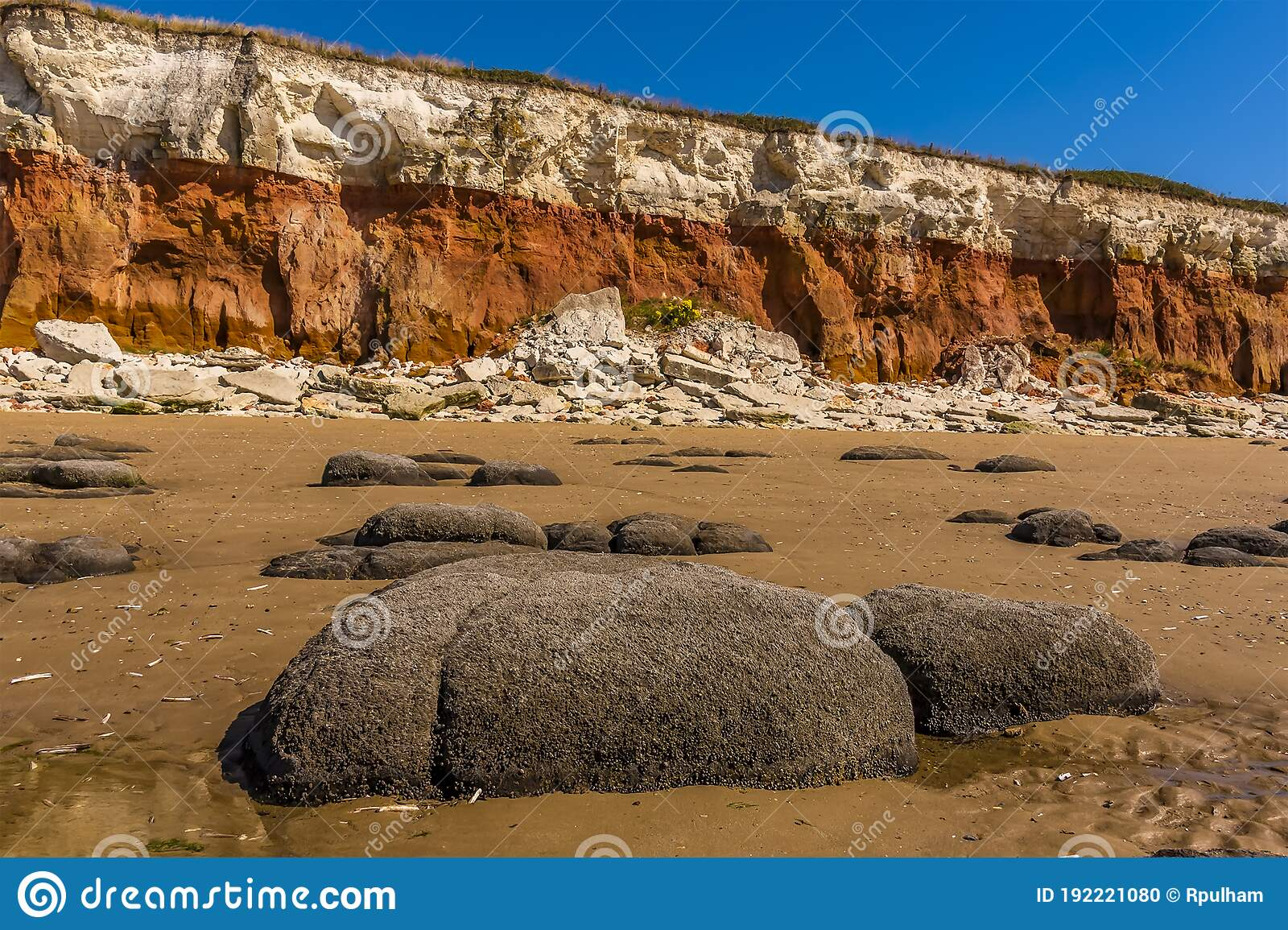 Sea eroded boulders in front of a chalk rock fall at the base of the cliffs at Old Hunstanton, Norfolk, UK