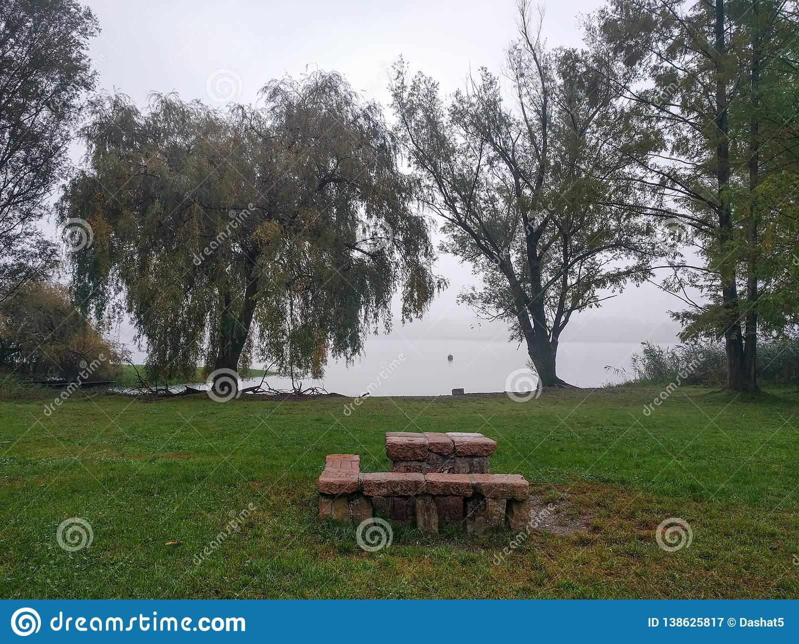 Recreation area with green field, bench and table near lake