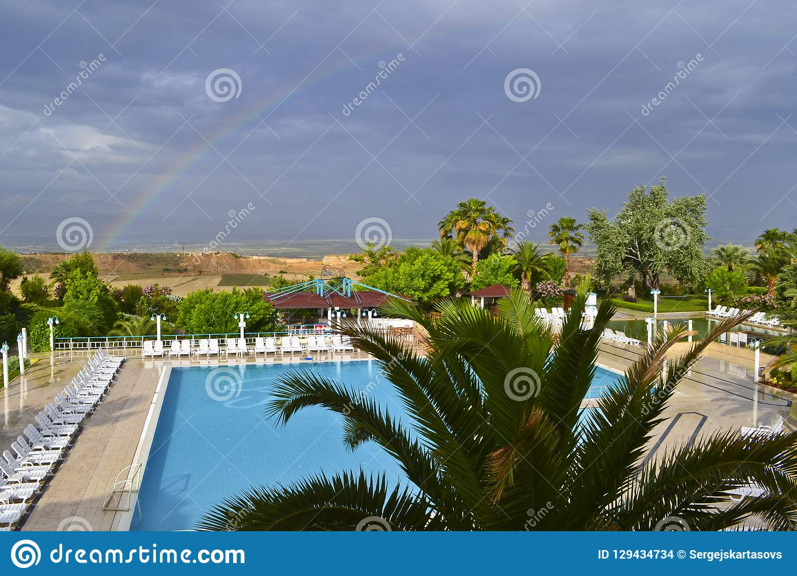 A view of a rural landscape, swimming pool and rainbow