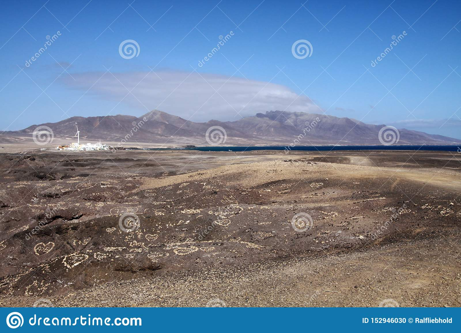 View on small white village, mountain range and spot of blue ocean over endless barren land, Fuerteventura, Canary Islands