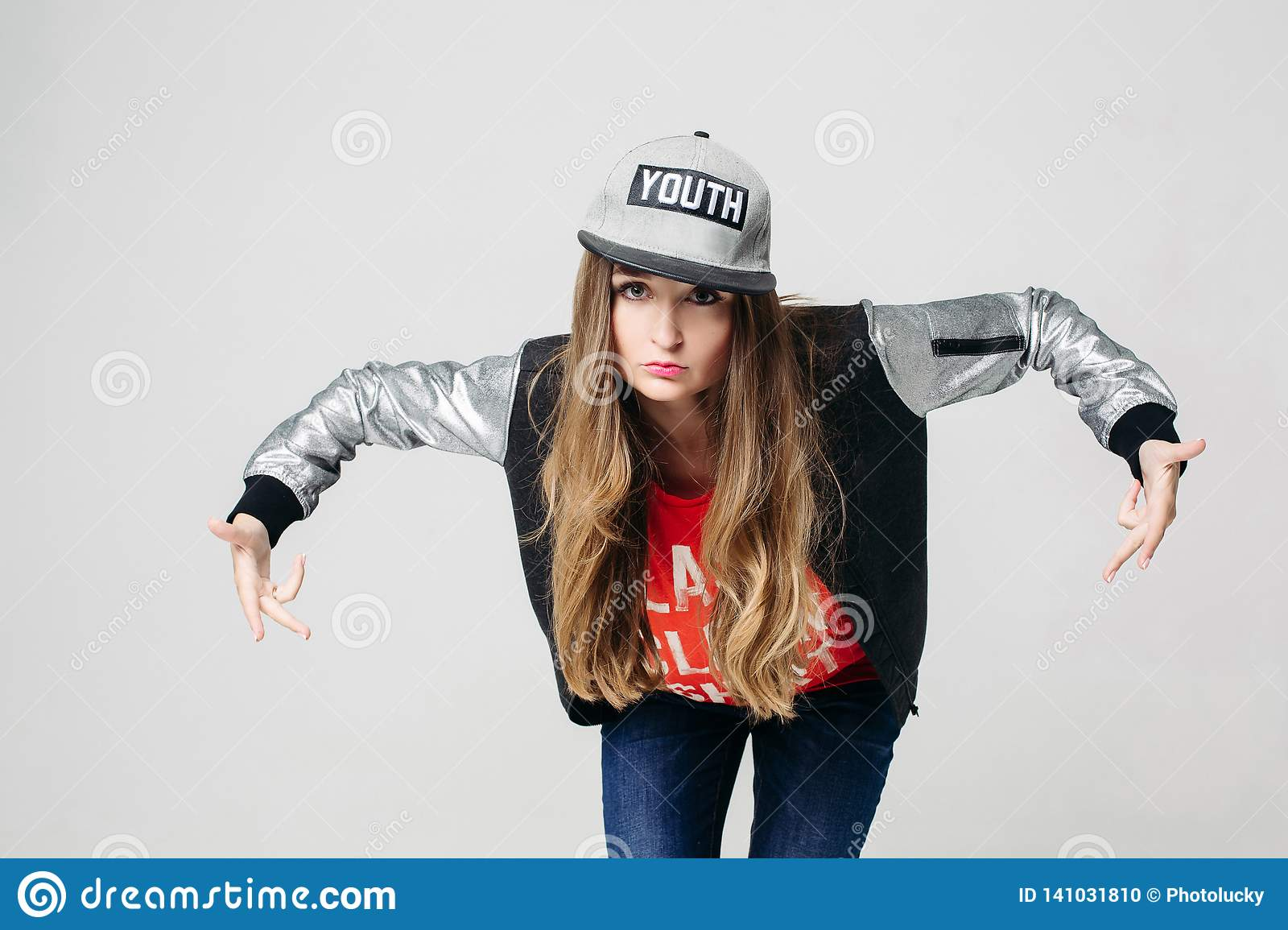 Swag Stylish Teenage Girl In Cap Posing With Hands Up. Stock