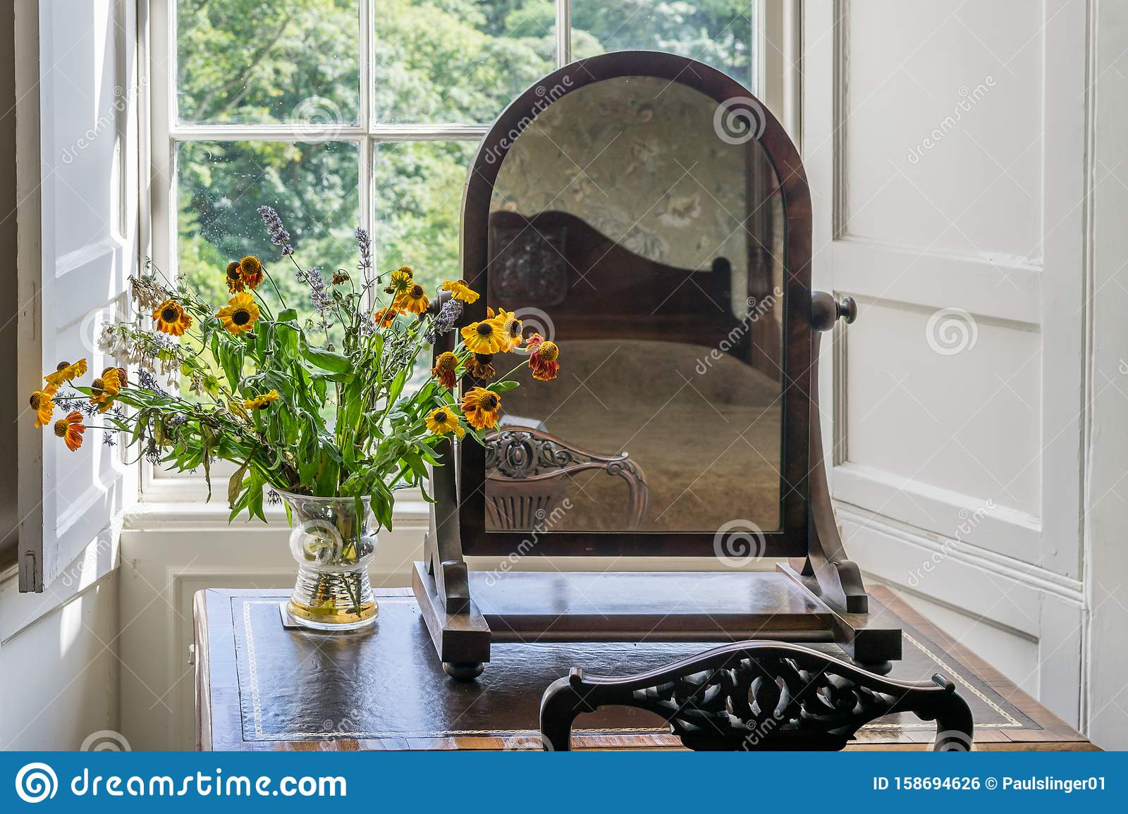 A View Of A Table Dresser With Chair And Mirror A Vase With Flowers In A Bay Window Area An Art Decor Scene Stock Photo Image Of Island Scene 158694626