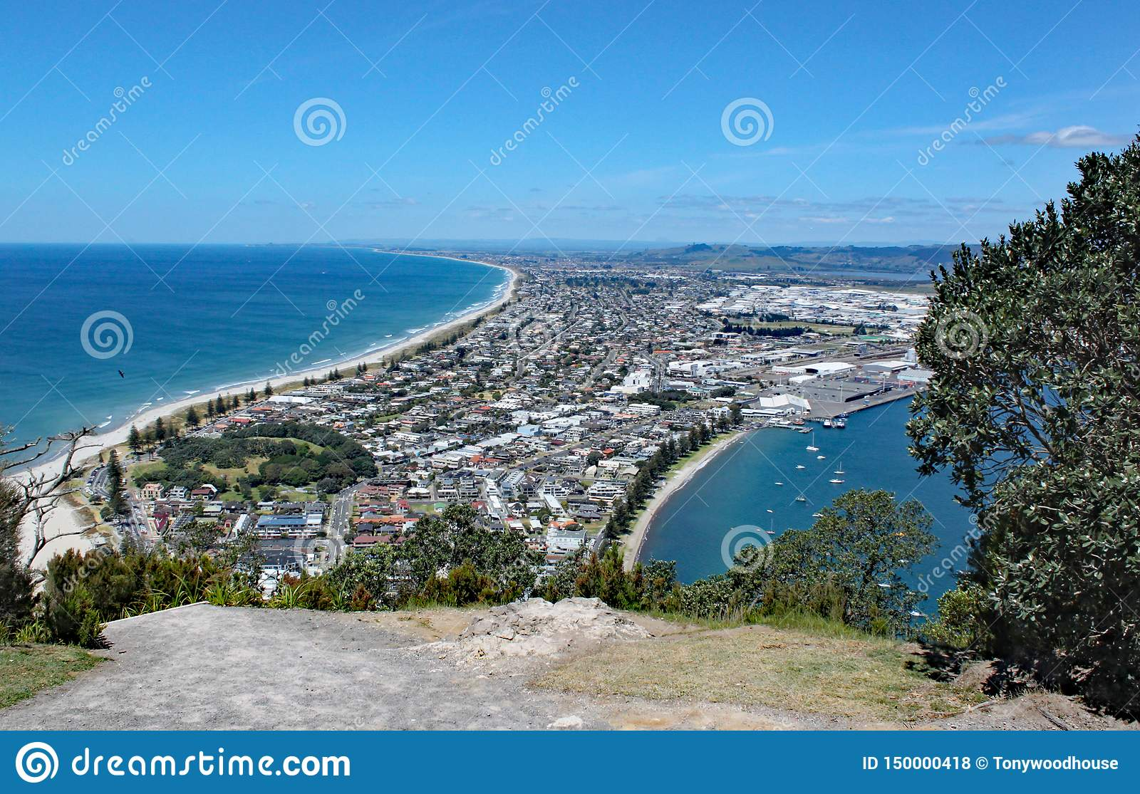 View of Tauranga from Mount Maunganui in New Zealand. Many people are on the beach enjoying the perfect weather