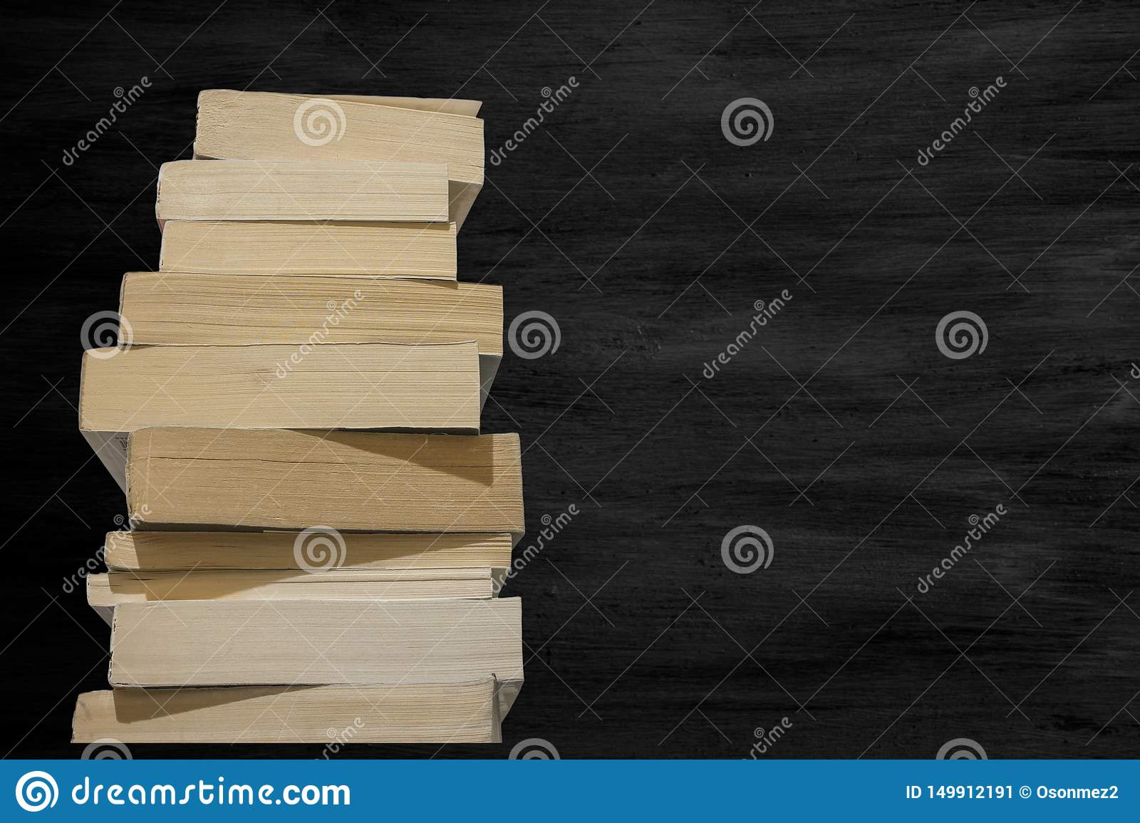 View of thick books lined up in a row and black chalk board in background