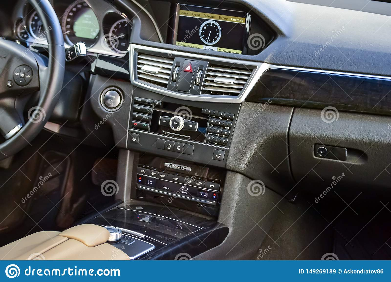 View to the white interior of Mercedes E-Class W212 with dashboard, clock, media system, front seats and shiftgear after