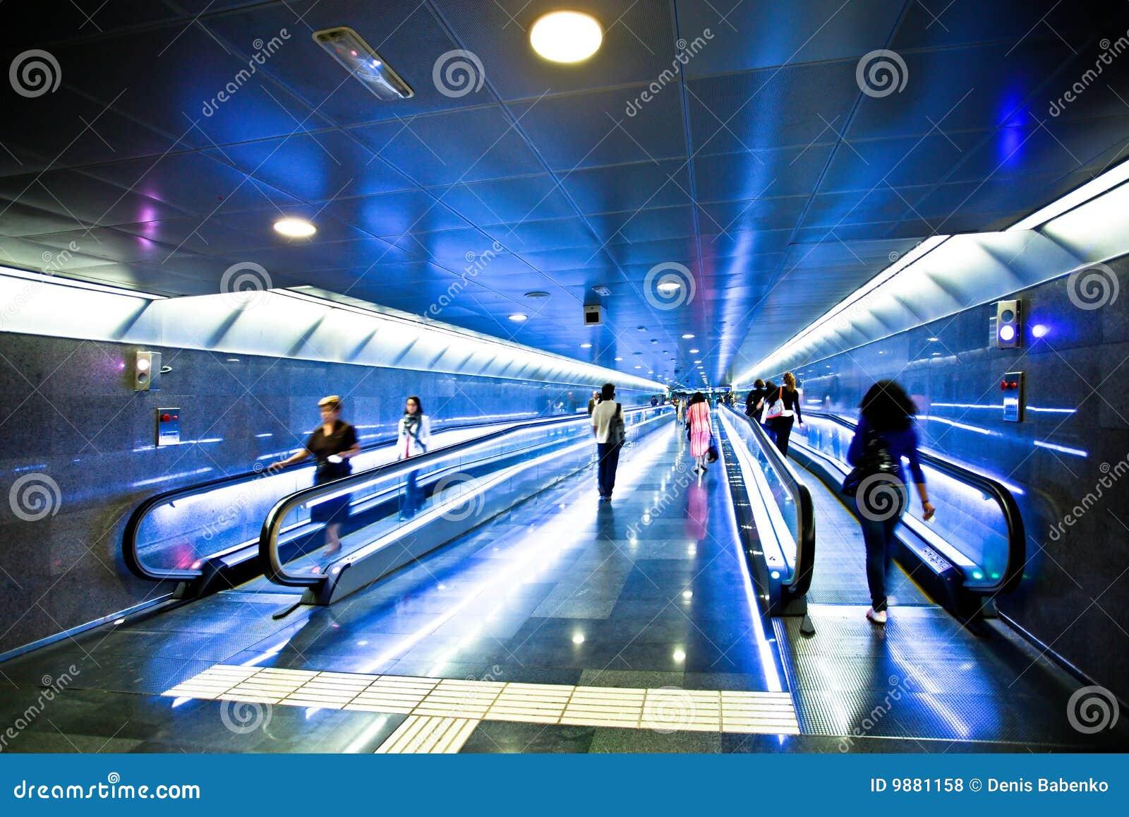 View to wide blue corridor with escalators