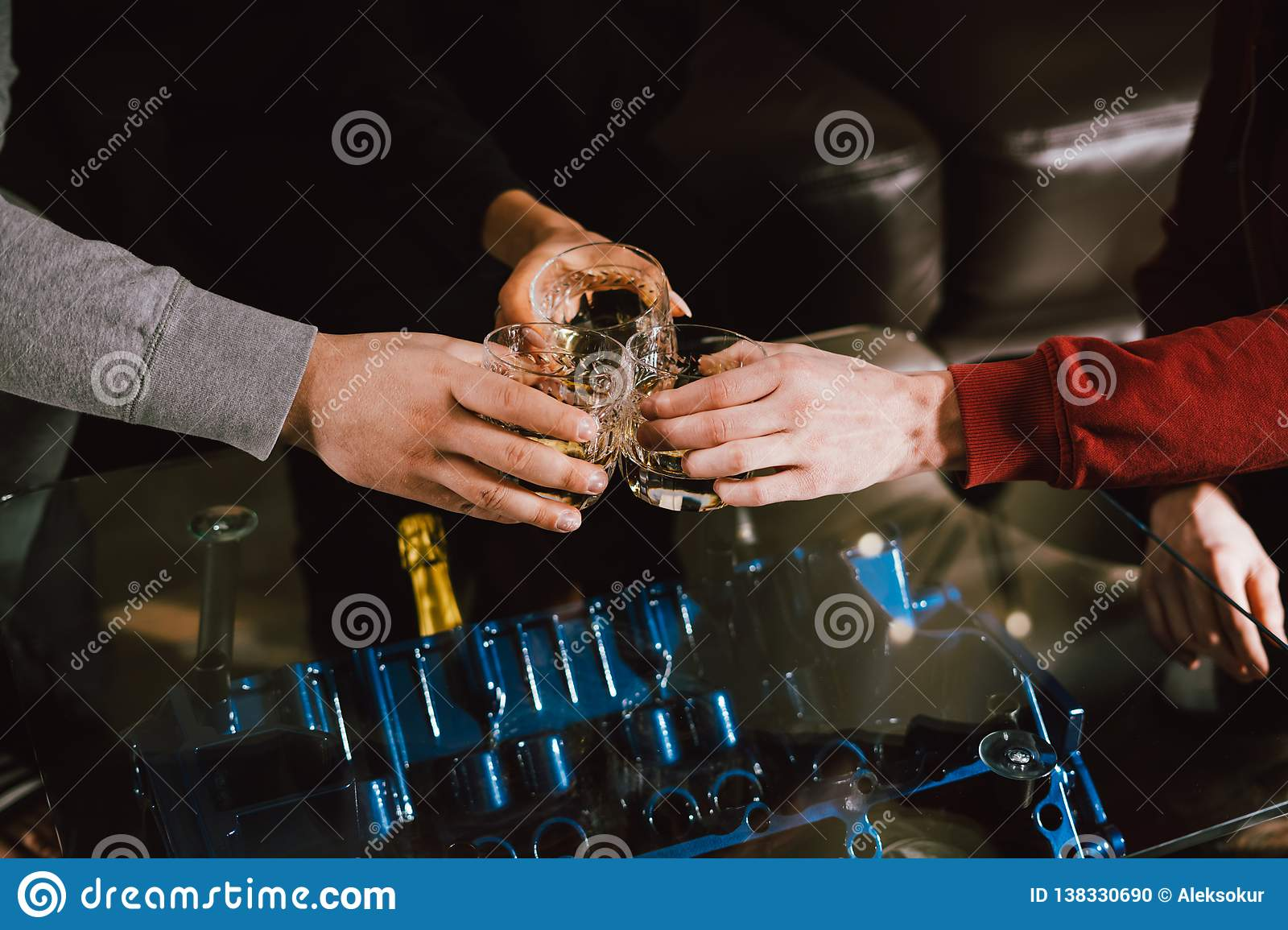 View from the top. Hands of people with glasses of whiskey or wine, celebrating and toasting of the wedding, meeting or other