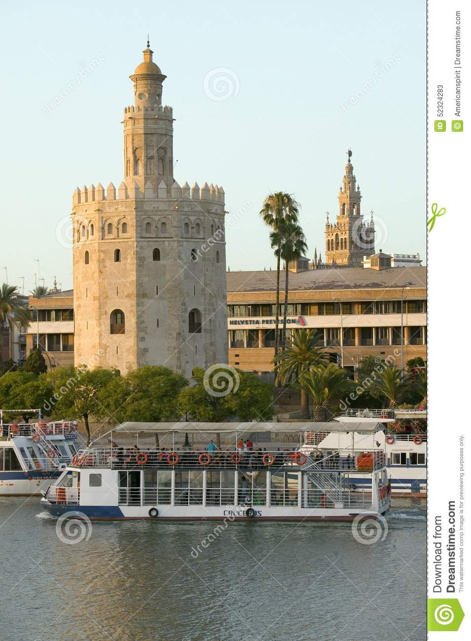 View of the tour boats and octagonal tower of Torre del Oro makes golden reflection on Canal de Alfonso of Rio Guadalquivir