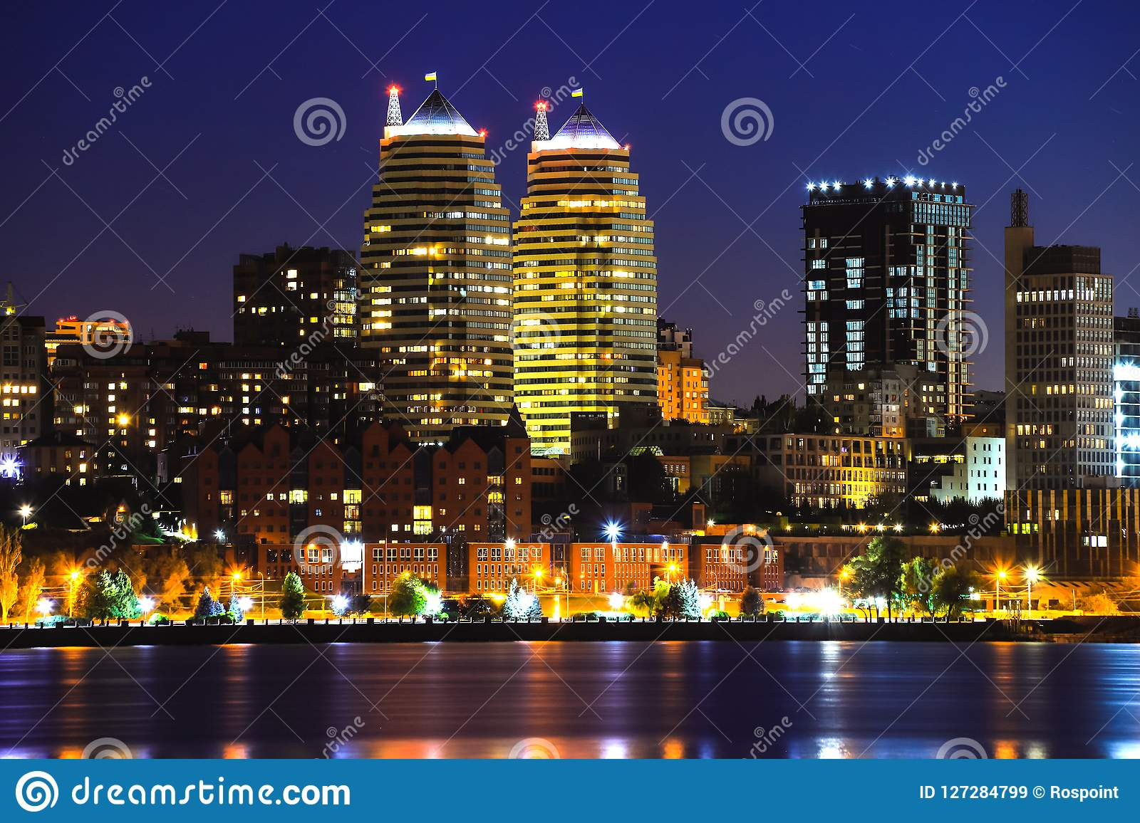 View of the towers, skyscrapers and buildings in Dnepr city at night, lights reflected on the river Dnieper, Ukraine.