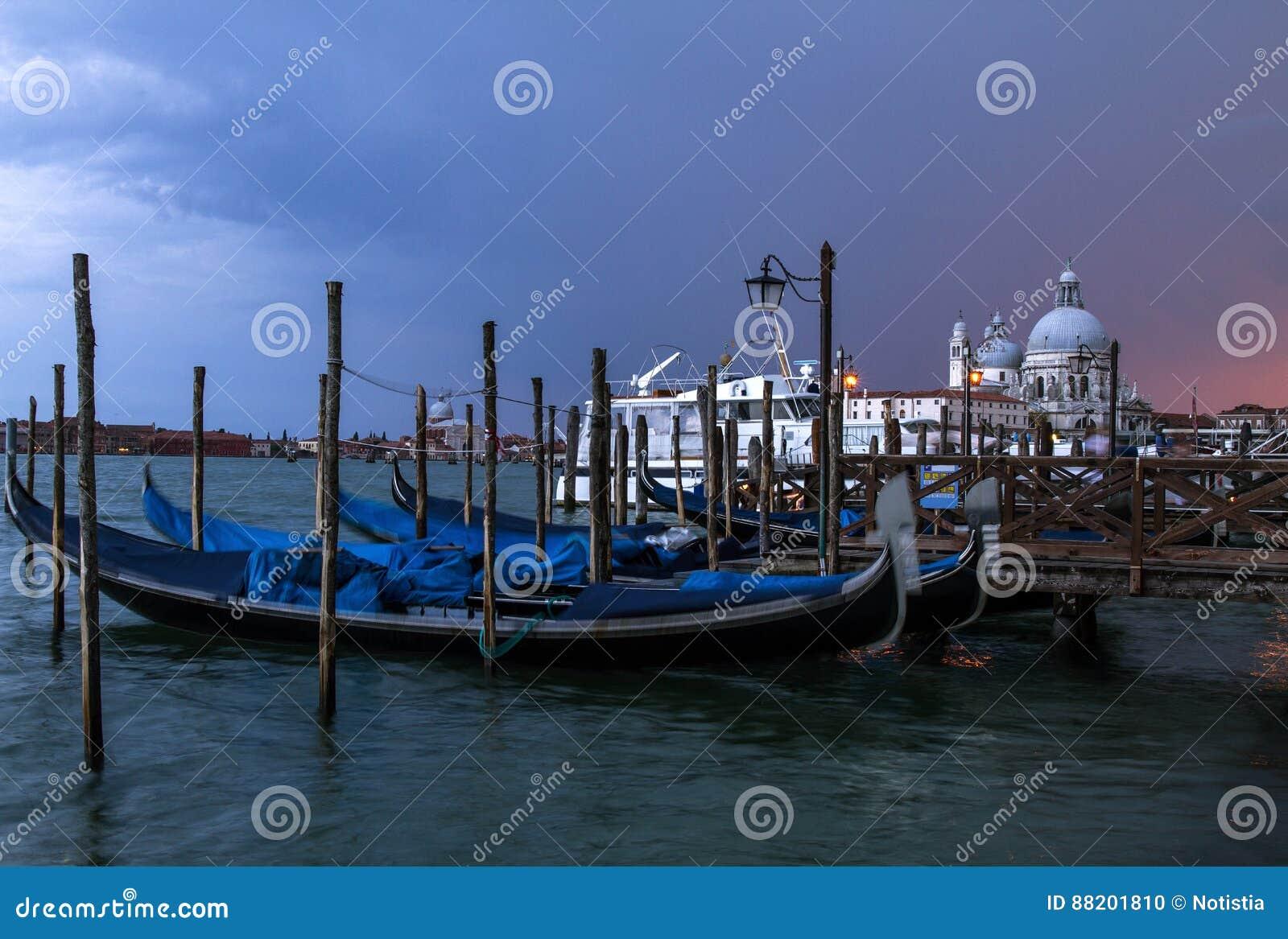 View of traditional Gondolas on Canal Grande with Basilica di Santa Maria della Salute church a cloudy evening . Venice , It