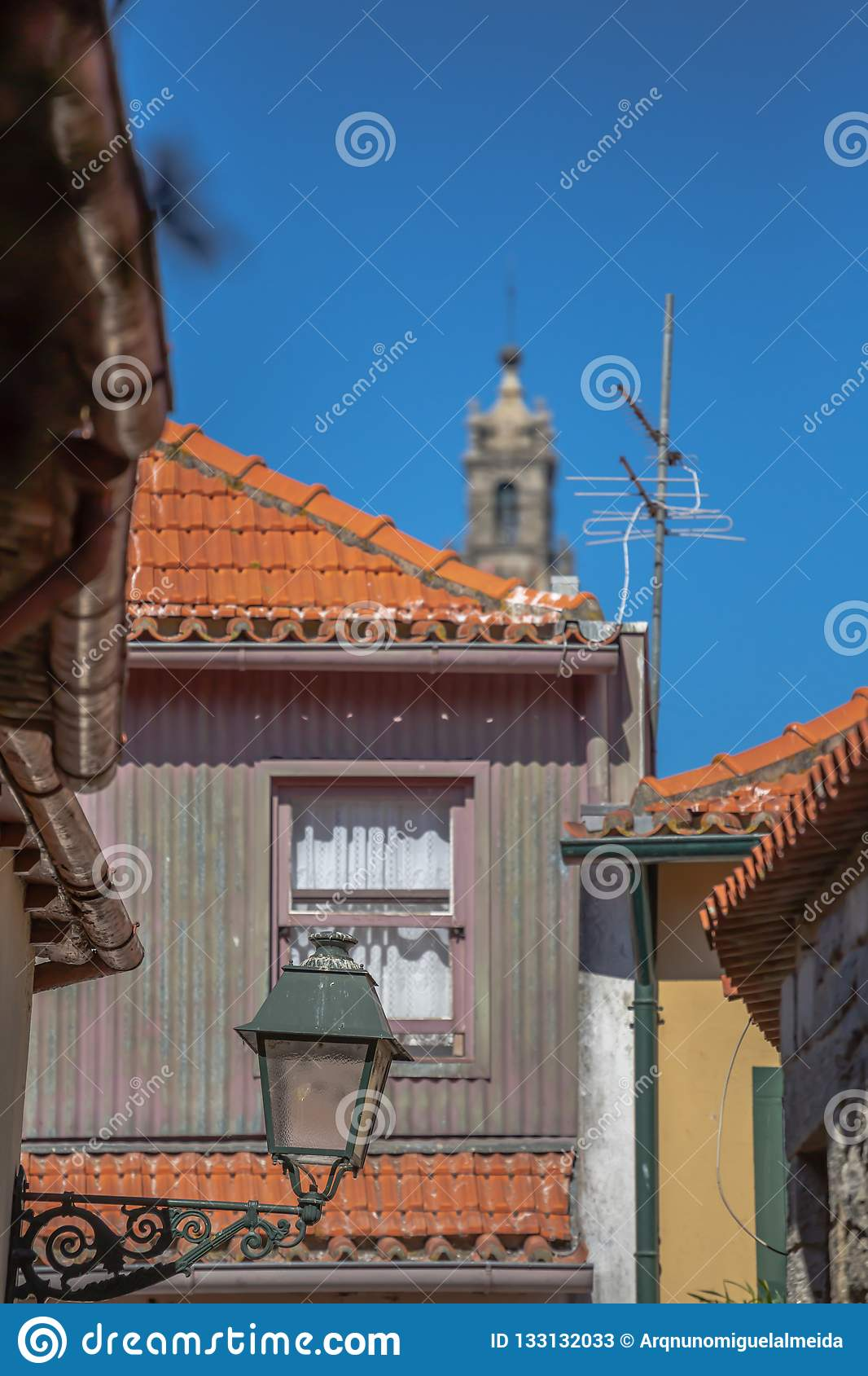 View at a traditional urban buildings on Porto downtown, blurred Clerigos tower on background