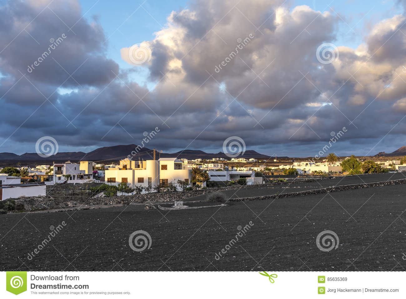 View on traditional whitewashed village with volcanos on the bac