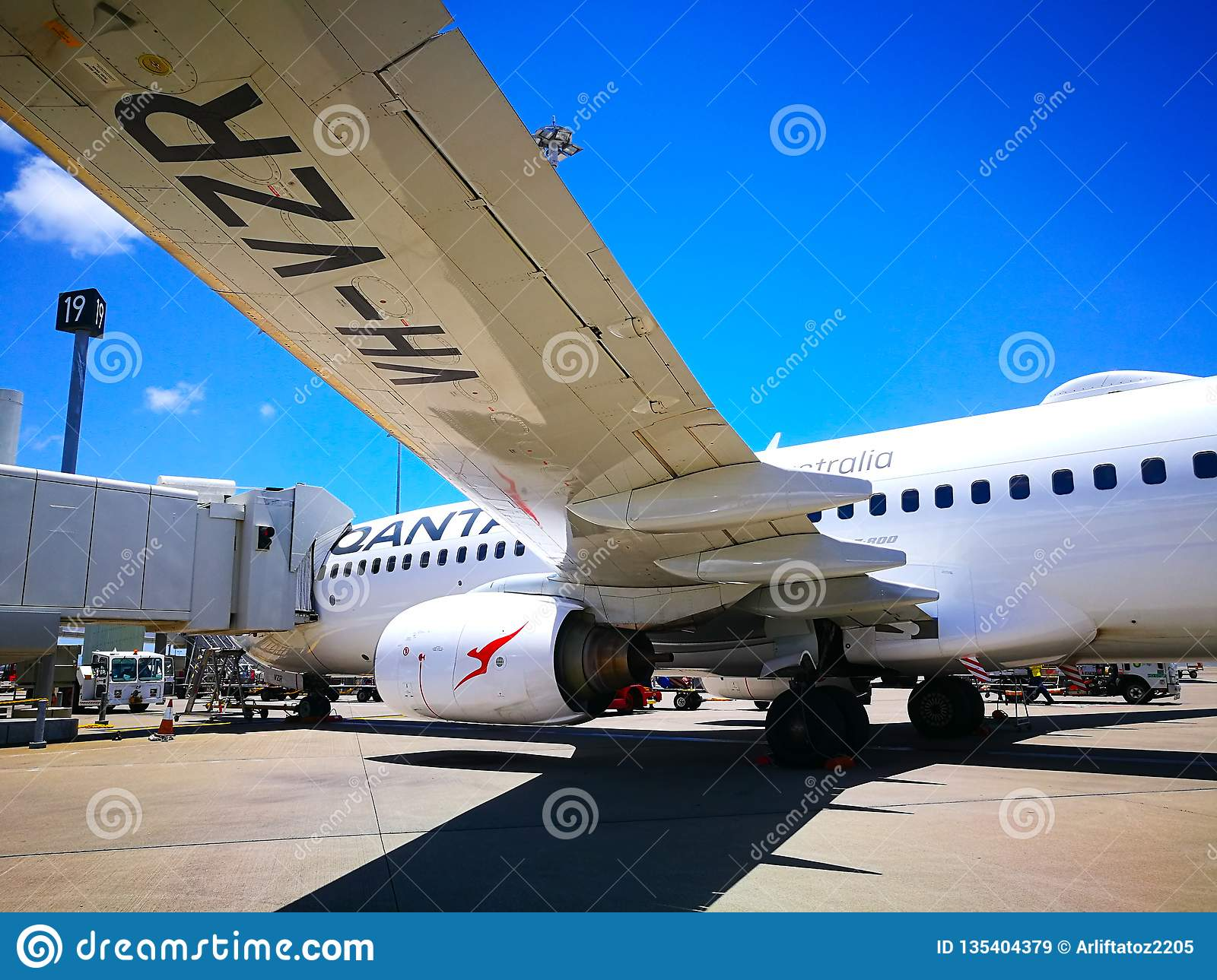 The view under the plane left wing of Qantas domestic airline Aircraft Type: Boeing 737 on the runway.