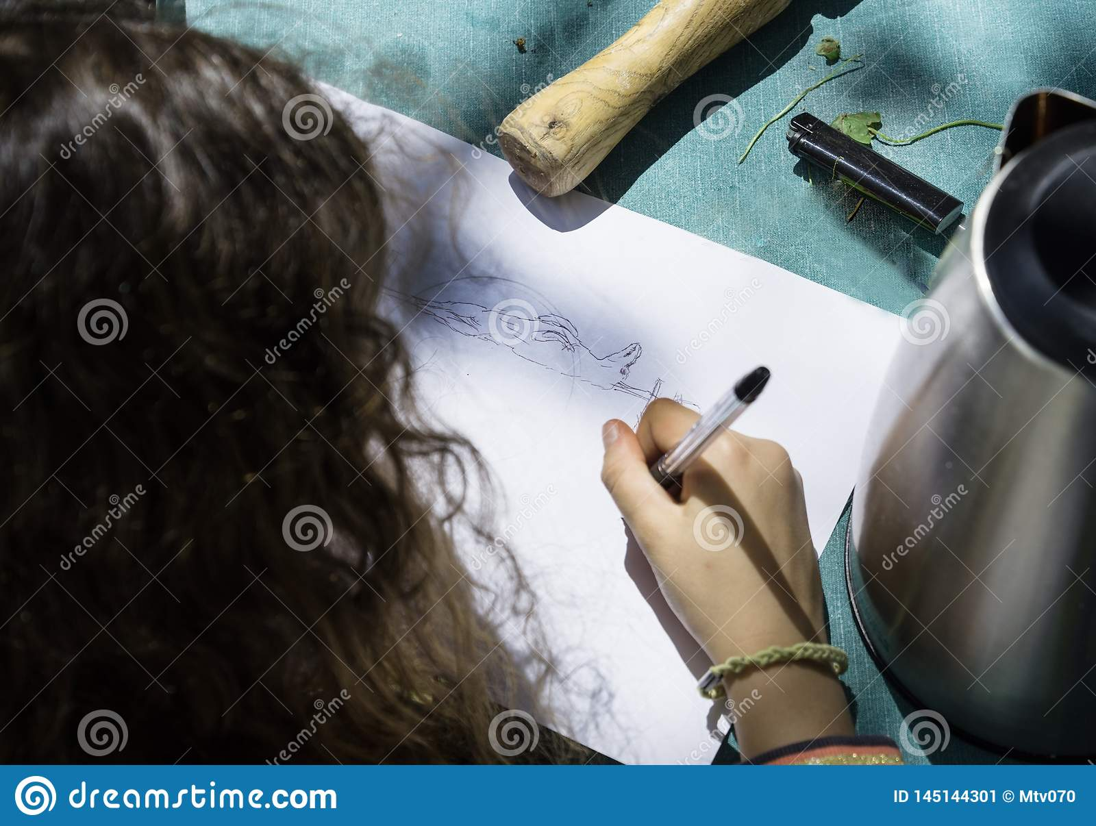 Girl draws Easter lamb on a spindle