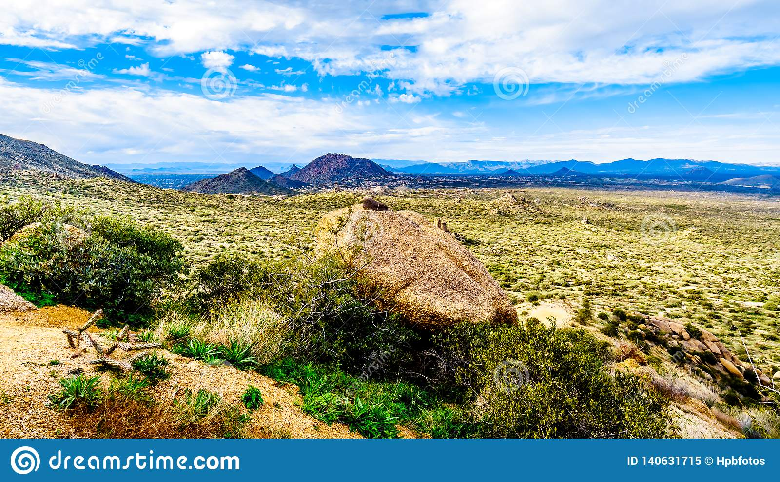 View of the Valley of the Sun and the rugged rocky mountains in the McDowell Mountain Range viewed from the Tom`s Thumb Trail