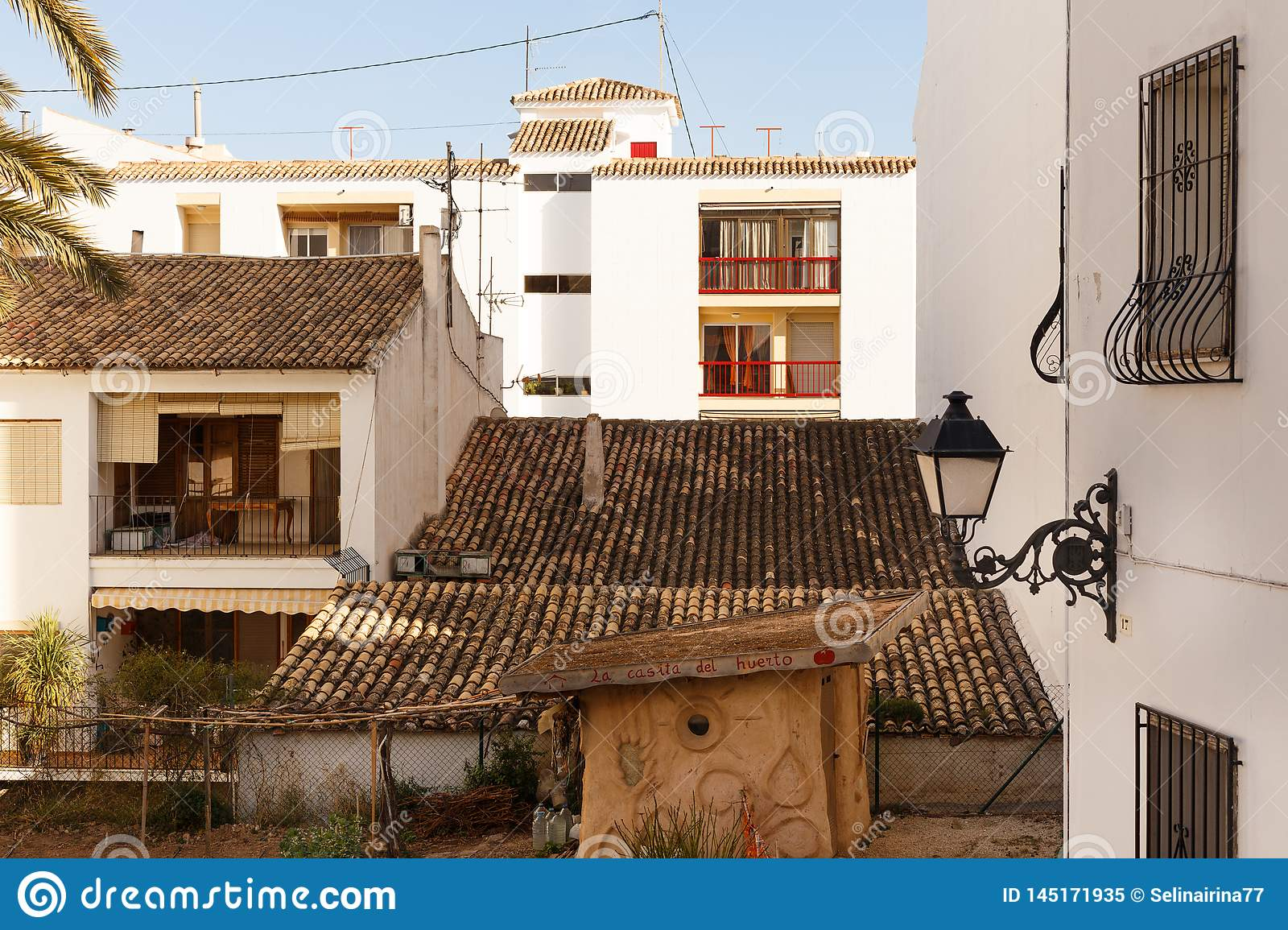 View of white houses with a tiled roof and balconies, and forged lantern in the old town of Altea, Spain on a hot sunny
