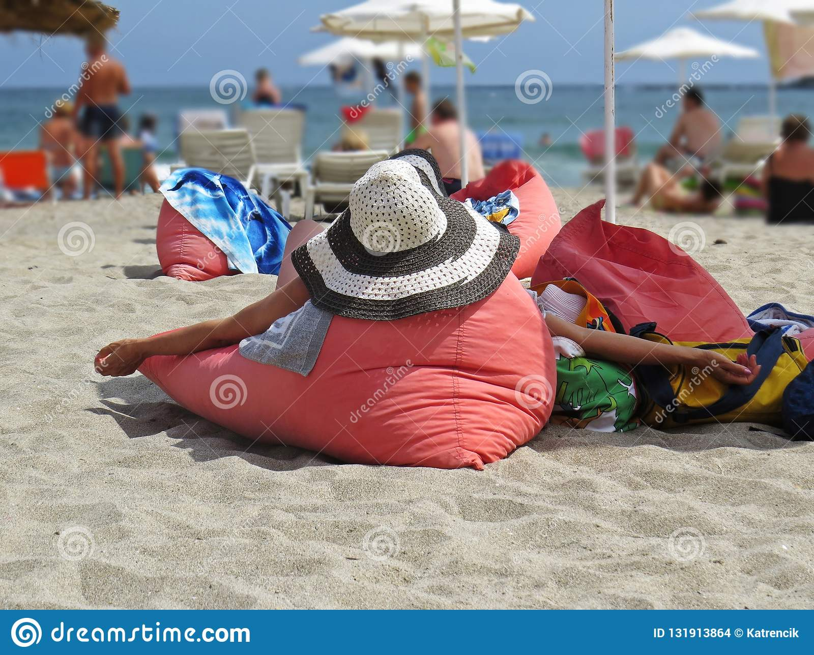 View at Woman from Back Lying on Red Pillow Cushion and Relaxing on Ocean Sand Beach Wearing Straw Hat During Summer Vacation