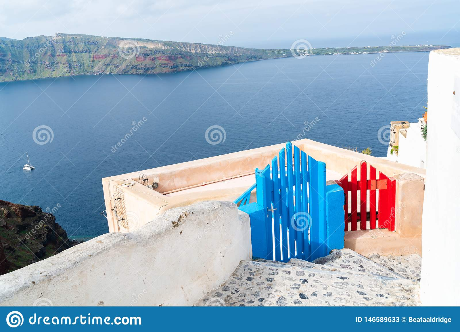 View of wooden blue and red gates and Aegean Sea in Oia, Santorini