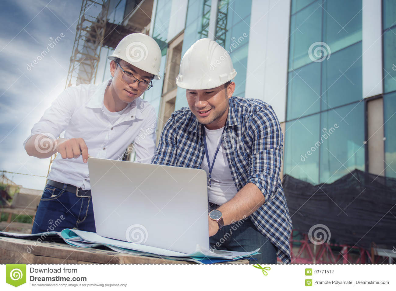 View of workers and architects who see details about construction on a computer.