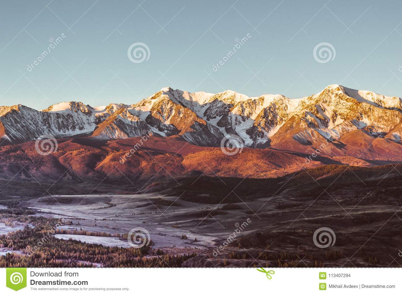 The views of the snowy peaks and the river valley at dawn.
