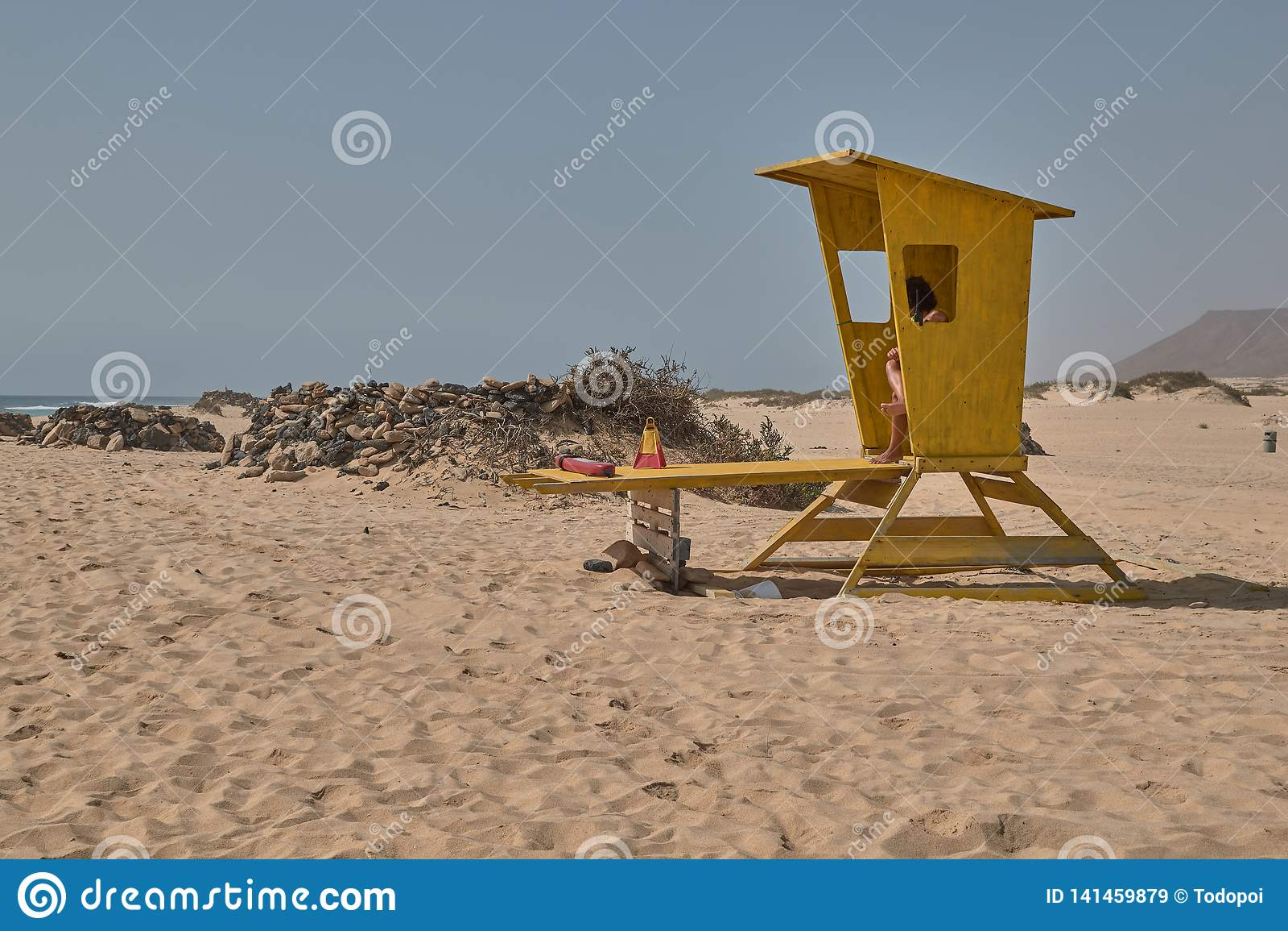 Vigilante nella tettoia gialla che esamina il mare nella spiaggia di Corralejo, Fuerteventura