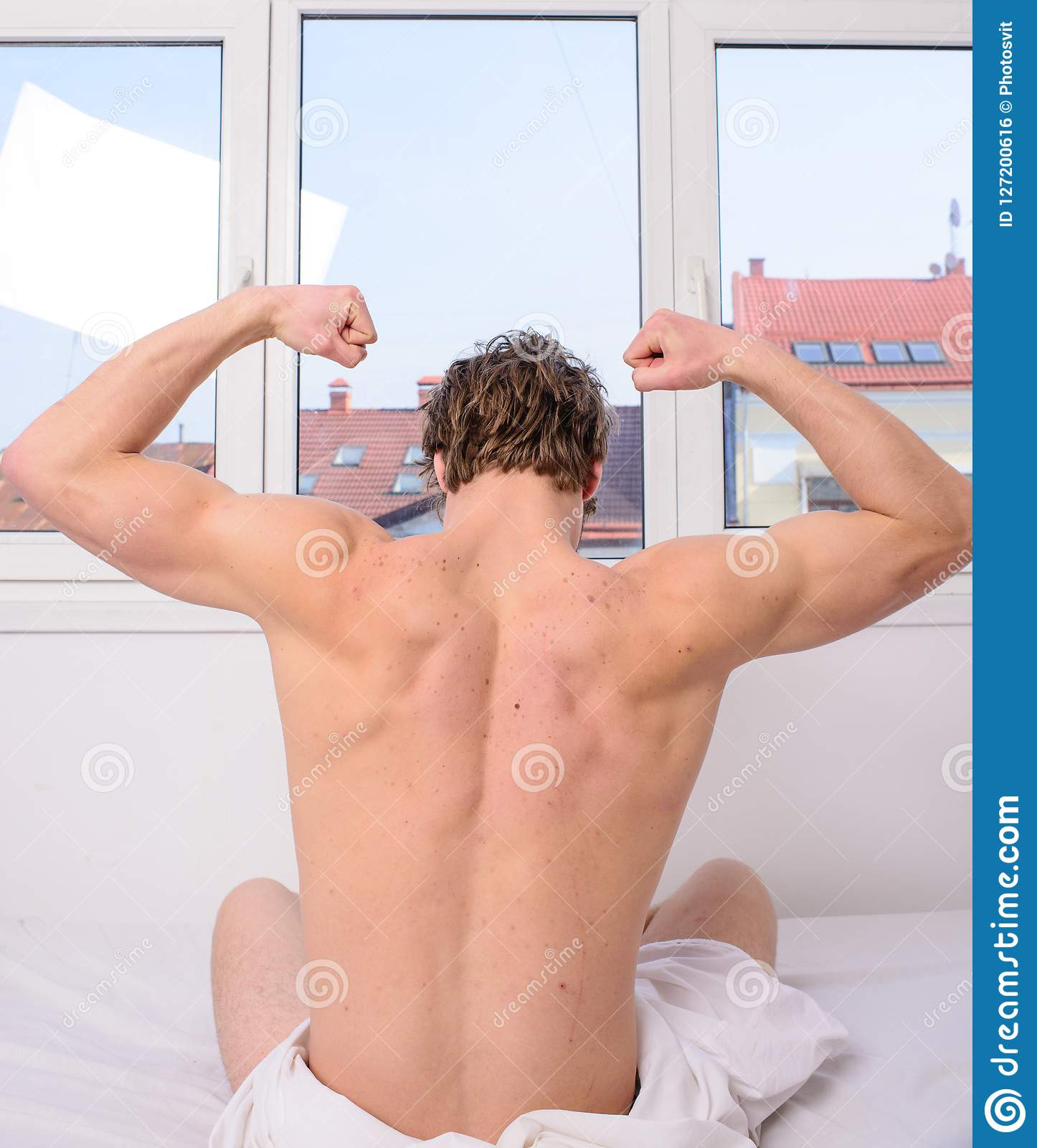 Vigorous exercise best but even light exercise better than no activity. Man muscular back stretching bed rear view. Get