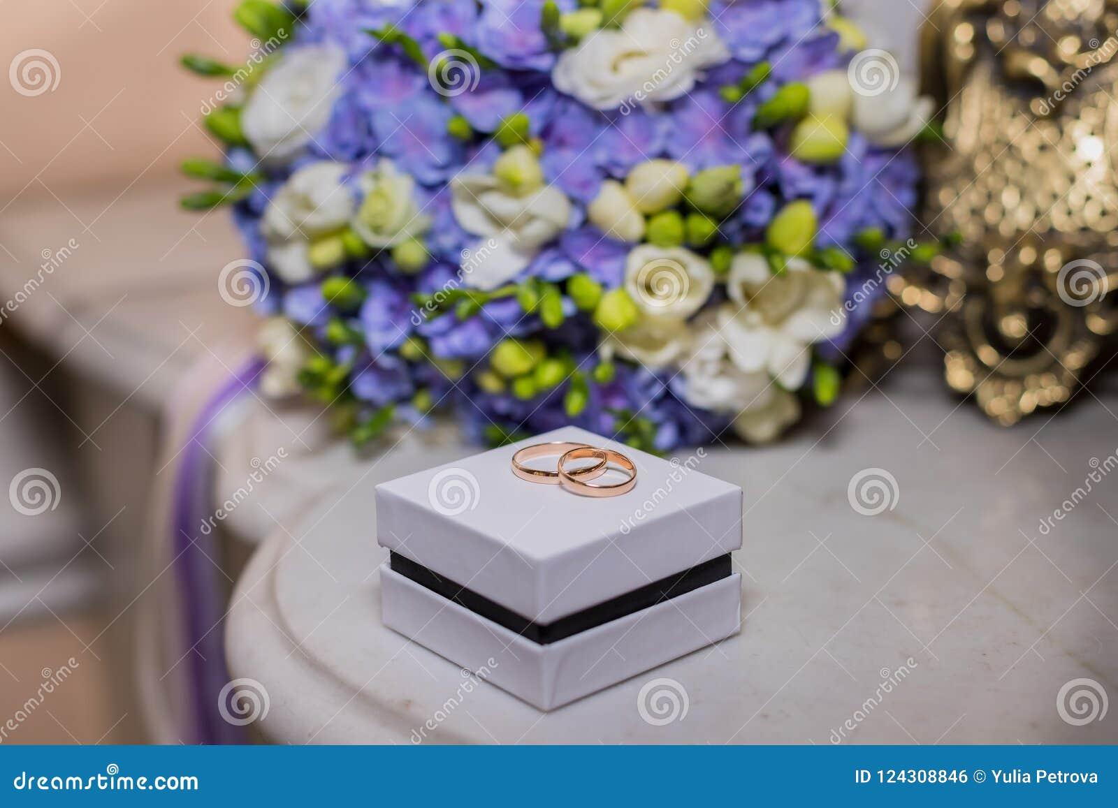 Vigselringar ligger på den vita asken på en härlig bukettbakgrund, som brud- tillbehör högtidlig händelse, festlig händelse