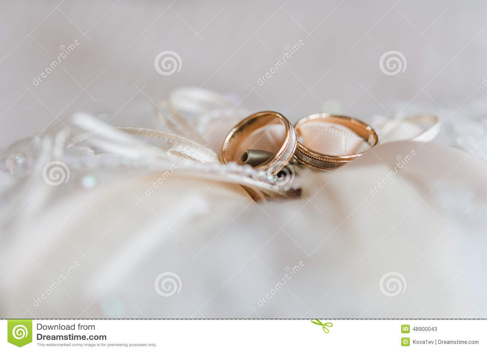 Vigselringar på en dekorativ kudde med pärlan och band i varma färger b6676898156b7