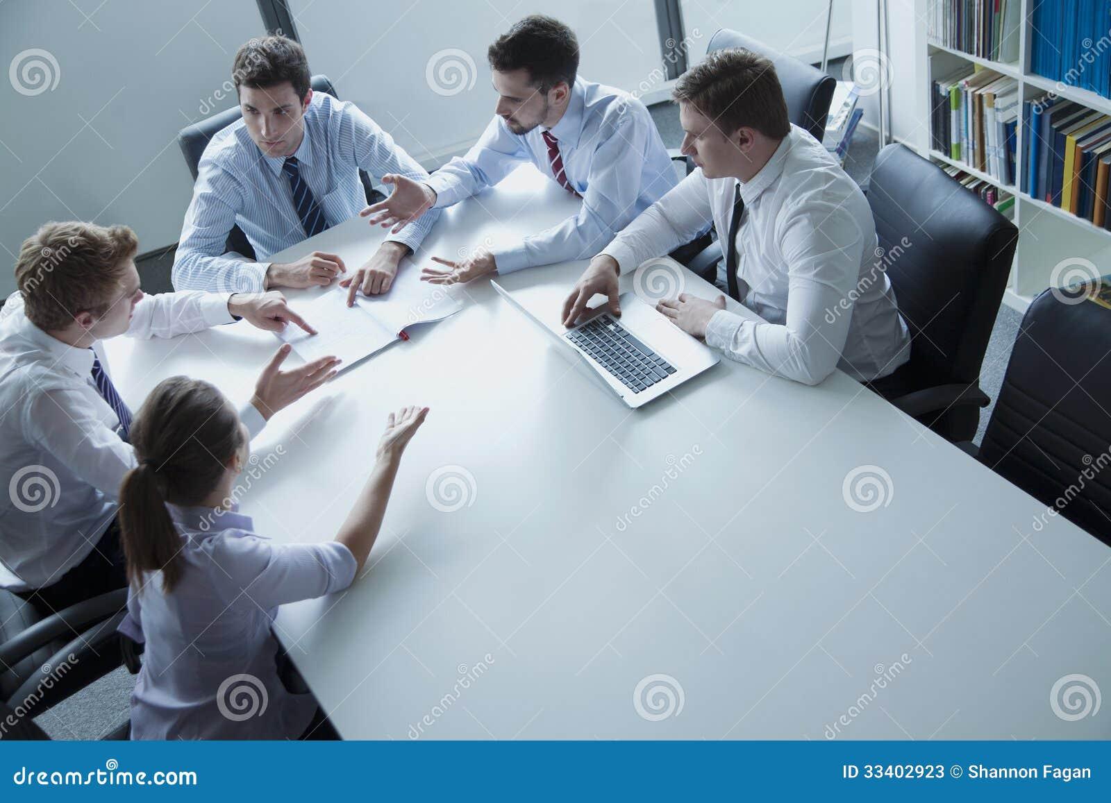 Vijf bedrijfsmensen die een commerciële vergadering hebben bij de lijst in het bureau