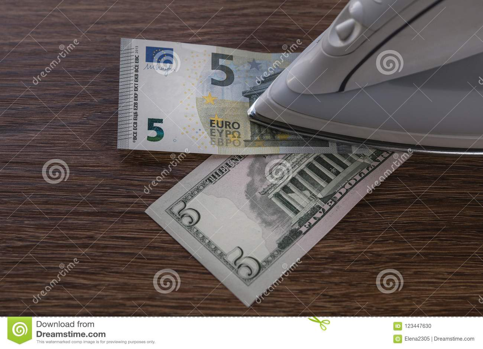 Vijf dollar en vijf-euro bankbiljetten onder het ijzer op houten lijst