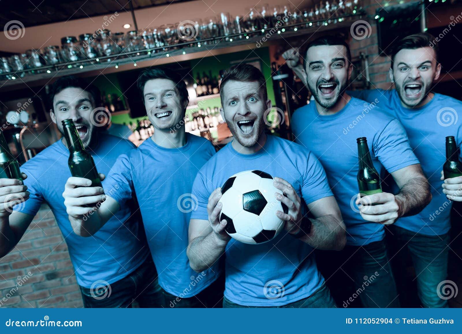 Vijf sportenventilators die bier drinken die en voor TV bij sportenbar vieren toejuichen