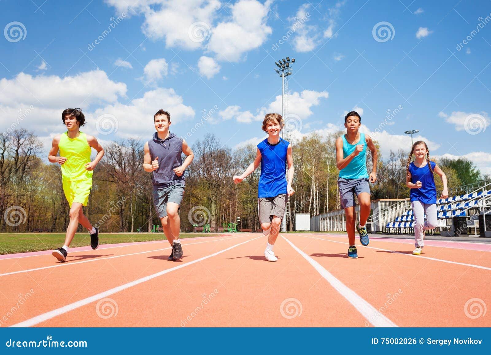 Vijf tienersprinters die samen op een spoor lopen
